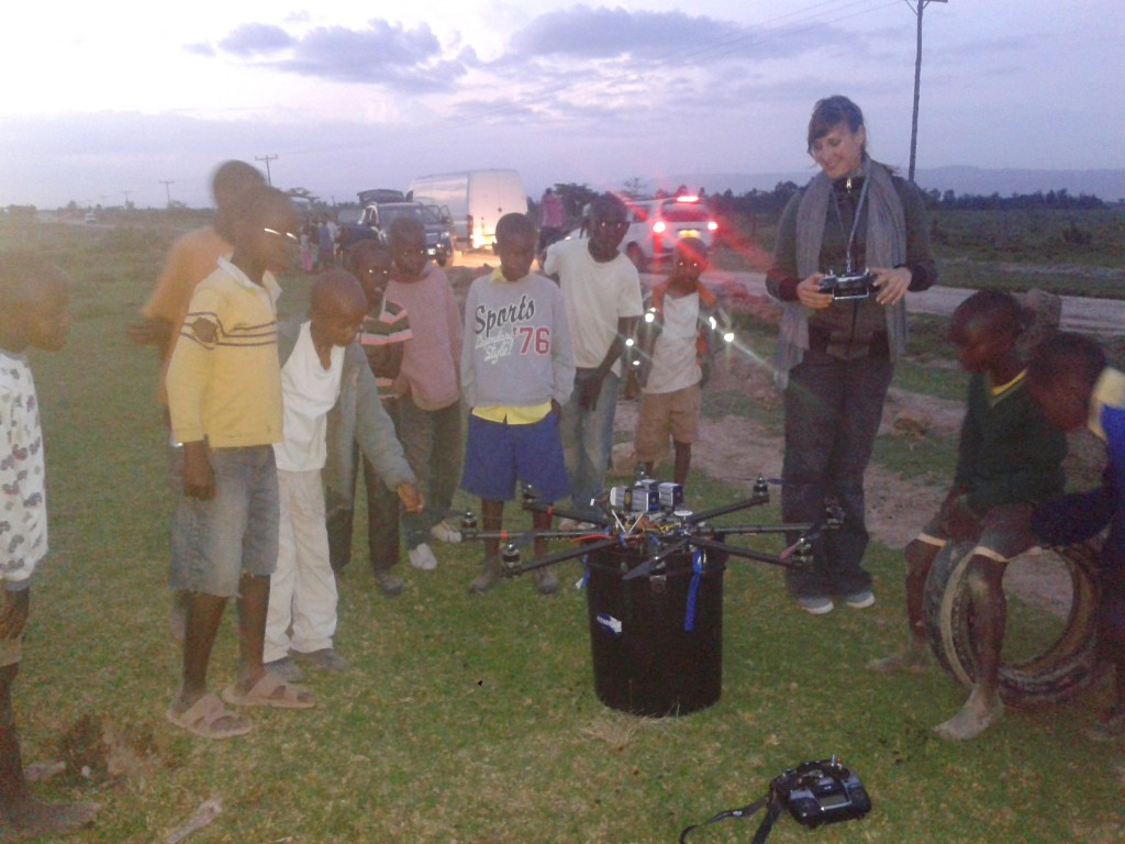 Helivideo camera operater with cinestar octocopter and African kids